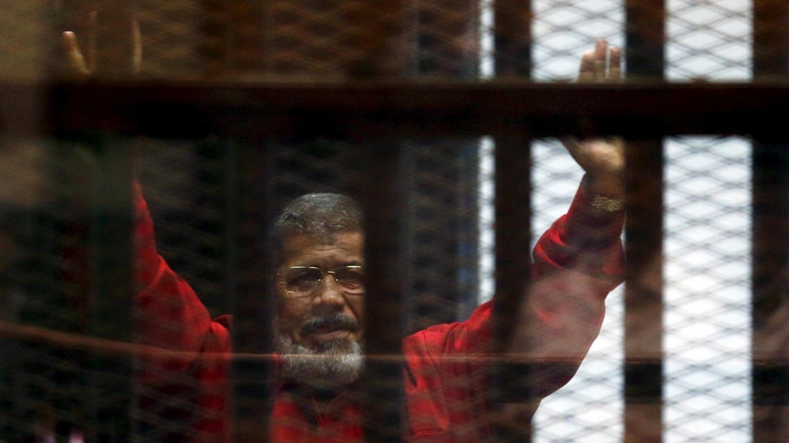 Egypt's deposed president Mohamed Mursi greets his lawyers and people from behind bars at a court wearing the red uniform of a prisoner sentenced to death, during his court appearance with Muslim Brotherhood members on the outskirts of Cairo, Egypt, June 21, 2015. REUTERS/Amr Abdallah Dalsh/File Photo