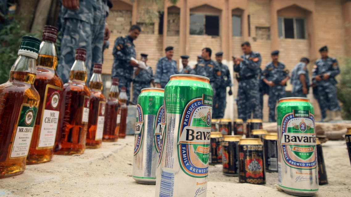 Iraqi policemen lay out cans of beer, alcohol, and weapons seized in a raid in the district of Tanouma on the outskirts of the southern Iraqi city of Basra, near the Iranian border on June 6, 2009. AFP