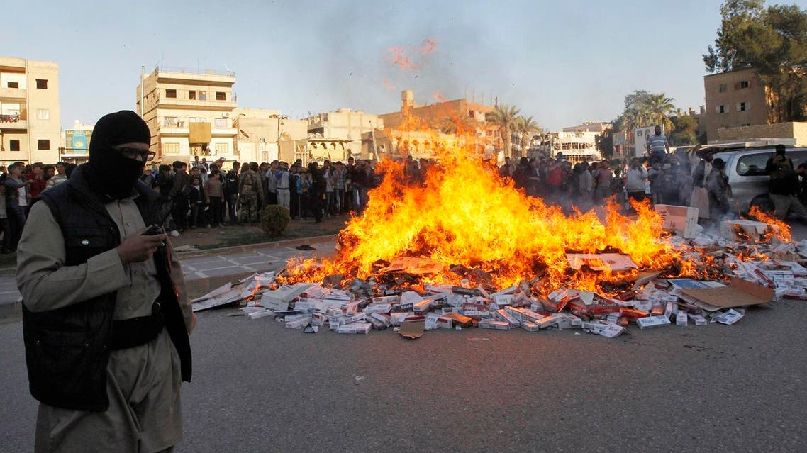 An ISIS fighter stands near burning confiscated cigarettes in the city of Raqqa April 2, 2014. (Reuters)