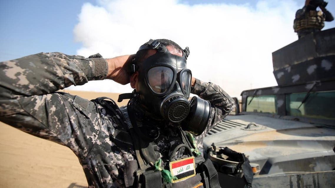 Members of the Iraqi forces wear a gas mask for protection as smoke billows in the background. (AFP)