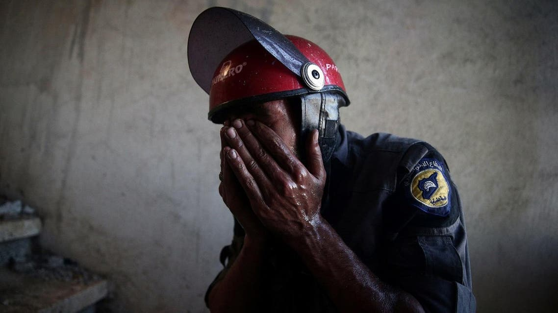 A Civil Defence member rubs his eyes as he tries to put out a fire inside a building after shelling in the rebel held besieged town of Douma, eastern Ghouta in Damascus. (Reuters)