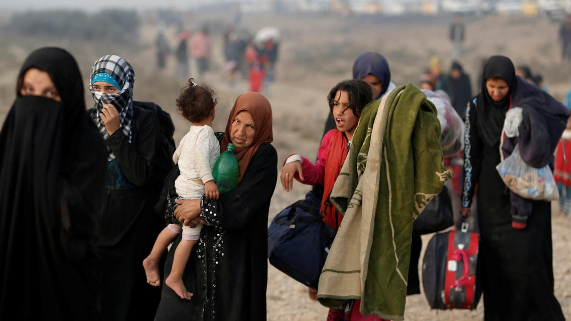 A newly displaced woman carries her child at a check point in Qayyara, east of Mosul, Iraq October 26, 2016. reuters