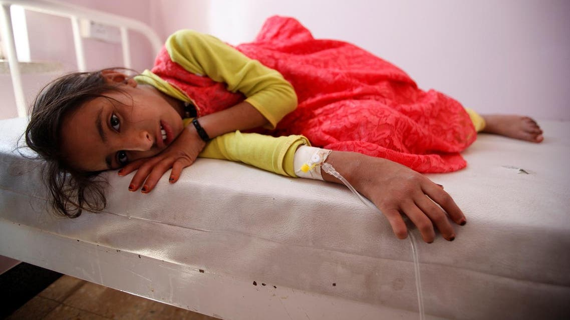 A girl lies on a bed at a hospital where she is receiving treatment for cholera. (Reuters)