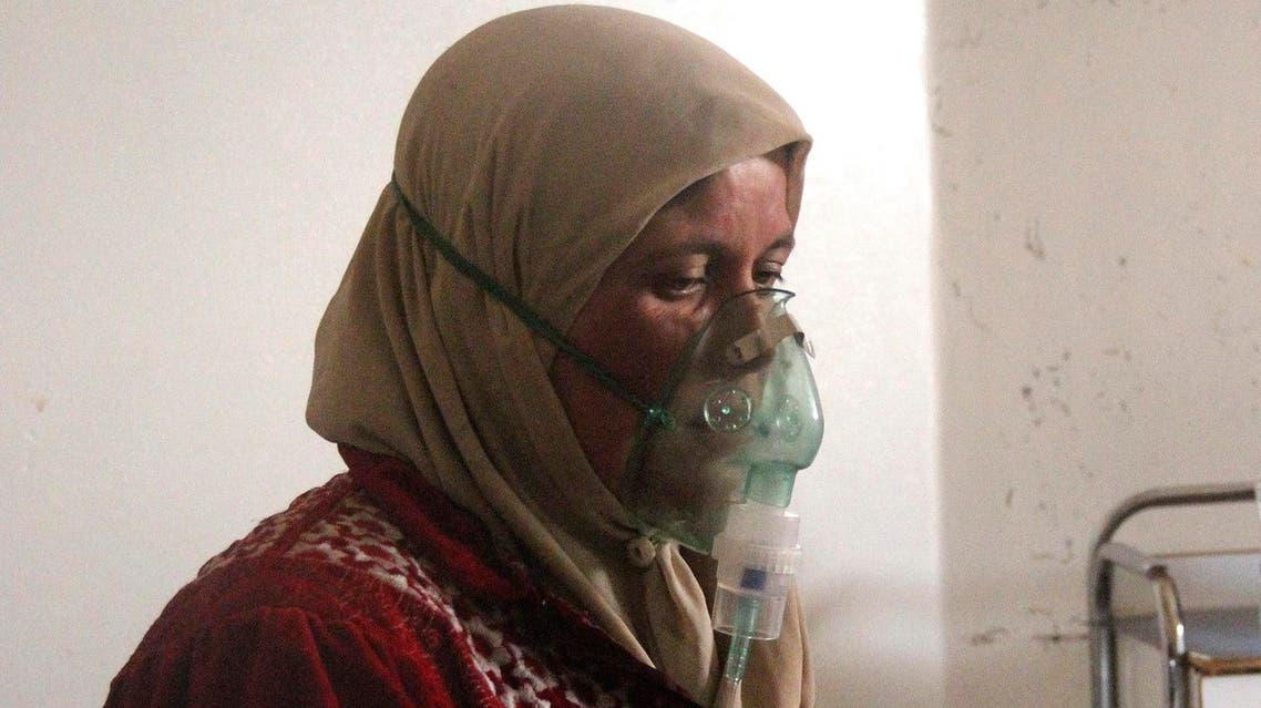 A woman, affected by what activists say was a gas attack, breathes through an oxygen mask inside a field hospital in Kfar Zeita village in the central province of Hama. (Reuters)