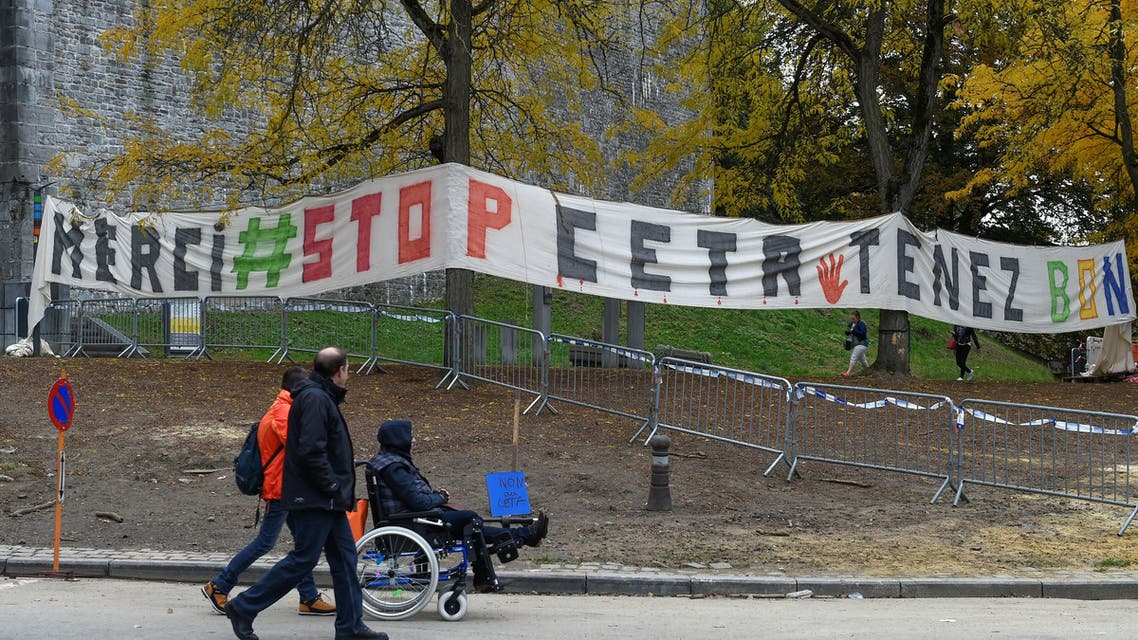People walk in front of a banner placed close to the Walloon parliament during a plenary debate on the EU-Canada Comprehensive Economic and Trade Agreement (CETA), in Namur on October 28, 2016. Parliament in Belgium's Wallonia region approved a landmark EU-Canada free trade agreement after marathon talks produced a compromise clearing the way for the European Union to sign the pact. By 58 votes to five, parliament in Namur south of Brussels became the first of the country's three French-speaking communities to back the accord, allowing the Belgian government to give the EU its blessing to go ahead with the deal.  JOHN THYS / AFP