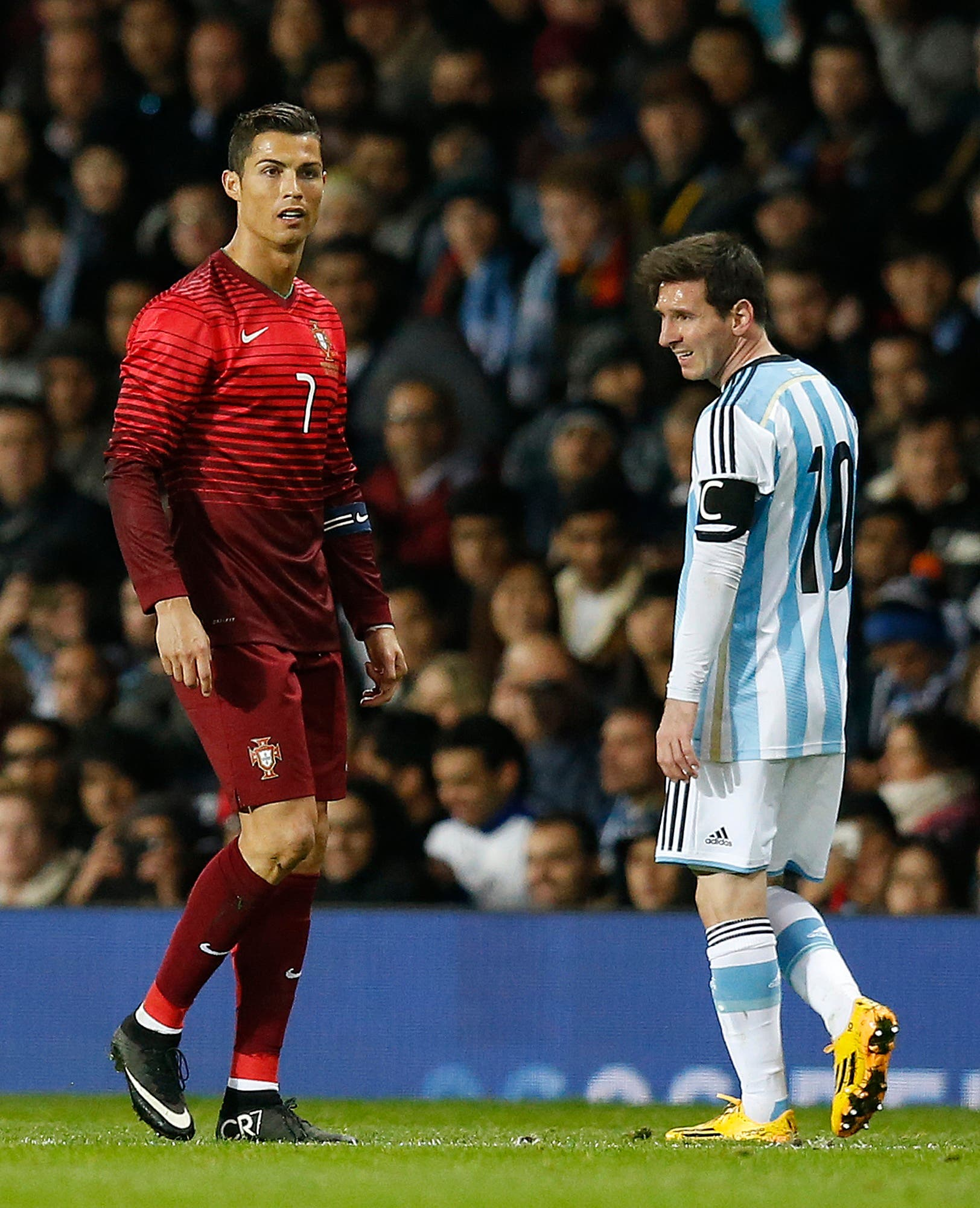 Cristiano Ronaldo of Portugal, left, and Lionel Messi of Argentina stand next to each other during their International Friendly soccer match at Old Trafford Stadium, Manchester, England, Tuesday Nov. 18, 2014. (AP)