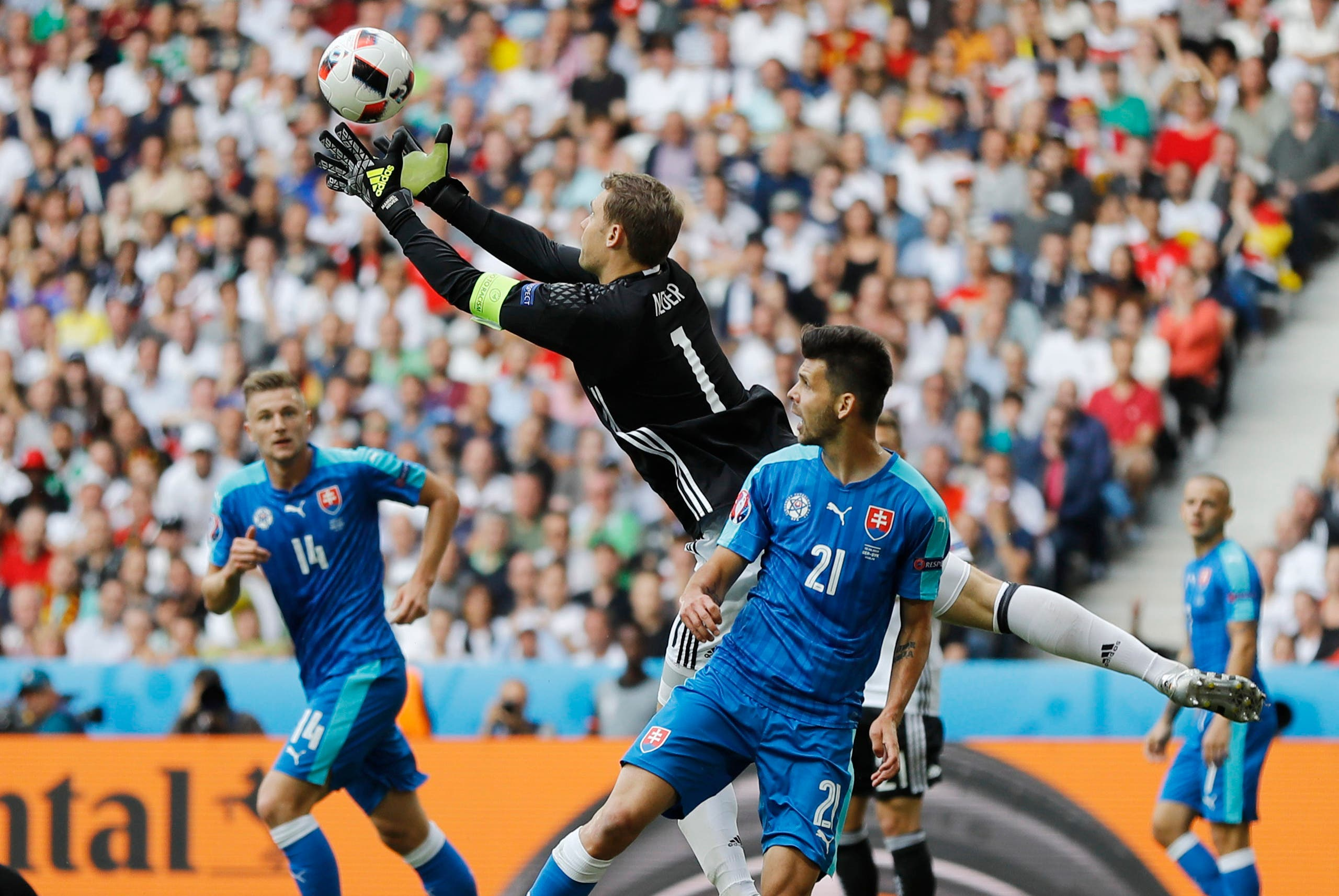 Germany goalkeeper Manuel Neuer reaches for the ball ahead of Slovakia's Michal Duris during the Euro 2016 round of 16 soccer match between Germany and Slovakia, at the Pierre Mauroy stadium in Villeneuve d'Ascq, near Lille, France, Sunday, June 26, 2016. (AP)