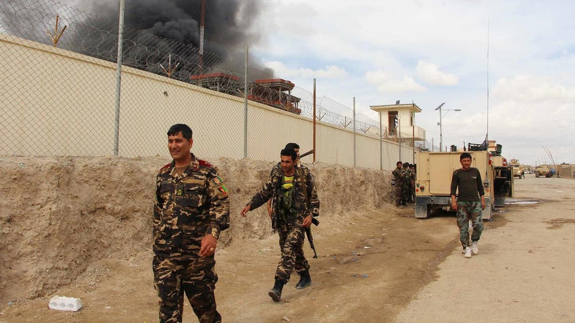 In this March 9, 2016 file photo, smoke rises from a building, where Taliban insurgents hide during a fire fight with Afghan security forces, in Helmand province, Afghanistan. For the past month, the Taliban have held control over most of Afghanistan's Helmand province, where the majority of the world's opium is grown -- and as insurgent attacks intensify around the provincial capital, residents are blaming rampant government corruption for the rising militant threat. At an international aid conference in Brussels that closed Wednesday, Oct. 5, 2016, Afghanistan's leaders pledged to clamp down on graft, but corrupt officials have hollowed out national security forces and are alienating local populations. (AP Photo, File)