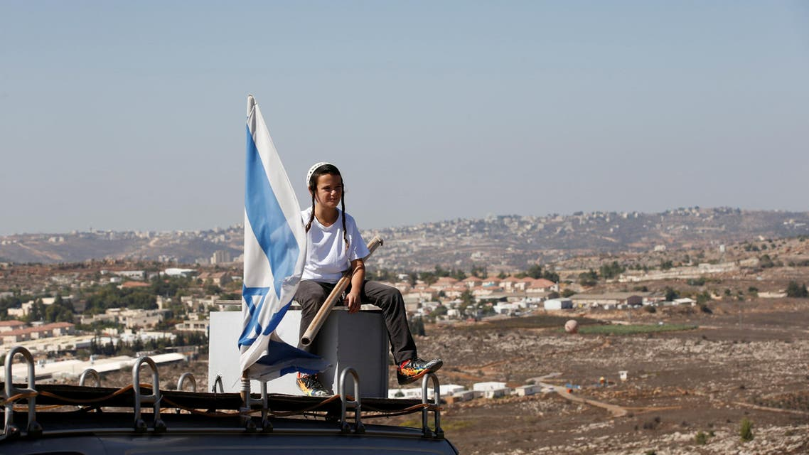 A boy sits near an israeli flag atop the roof of a vehicle at the entrance to the Jewish settler outpost of Amona in the West Bank, during an event organised to show support for Amona which was built without Israeli state authorisation and which Israel's high court ruled must be evacuated and demolished by the end of the year as it is built on privately-owned Palestinian land, October 20, 2016. REUTERS/Ronen Zvulun