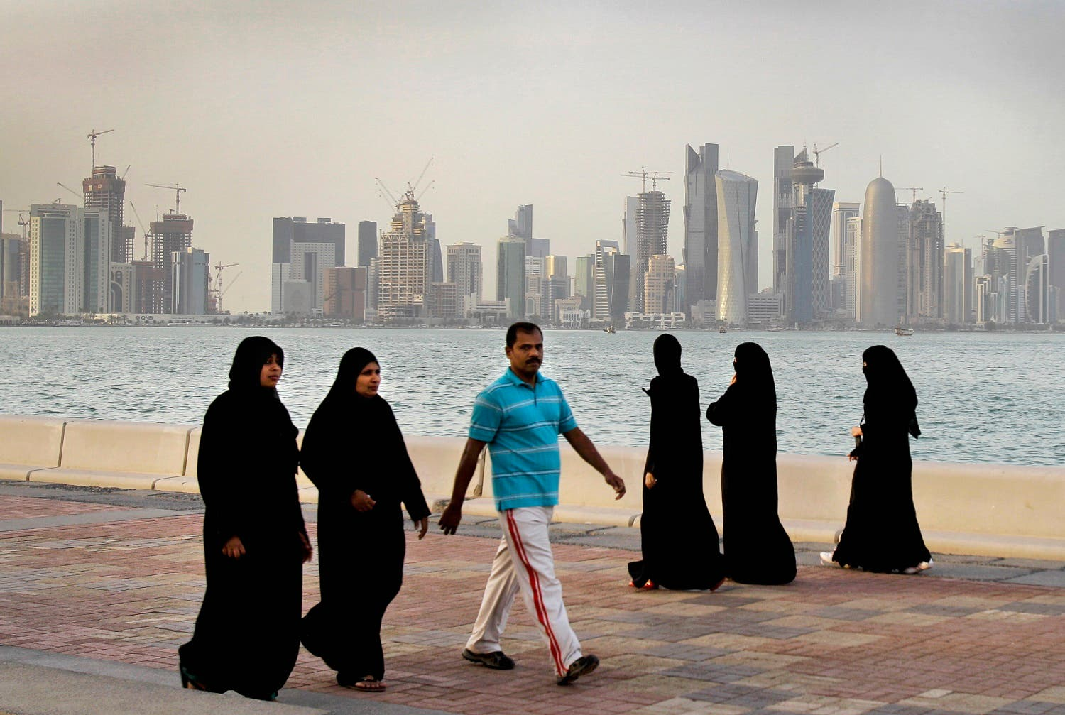 High-rise buildings of downtown Doha, photographed in the background, as women and a man walk by the sea in Doha, Qatar. (File photo: AP)