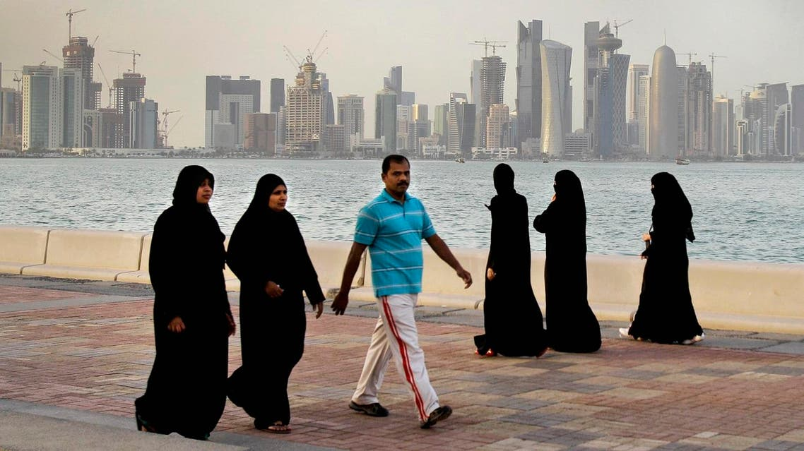"""In this Saturday, April 7, 2012 file photo, the new high-rise buildings of downtown Doha, photographed in the background as Qatari women and a man walk by the sea in Doha, Qatar. A worker on a Qatar World Cup stadium site has died in the first work-related fatality to be announced by organizers of the 2022 soccer tournament which has been dogged by concerns about labor conditions. Qatar has previously reported three deaths at stadium construction sites but said they were not """"work-related."""" (AP Photo/Kamran Jebreili, File)"""