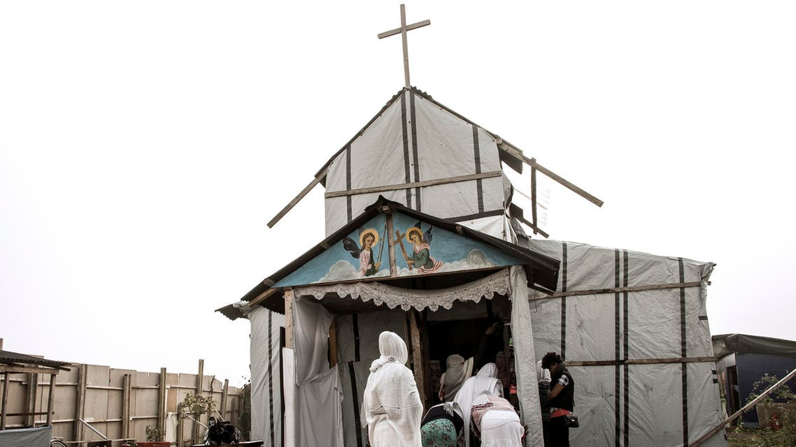 """Ethiopian Coptic migrants arrive for a mass at the makeshift Orthodox church in the Jungle"""" migrant camp, on October 30, 2016 in Calais, northern France. afp"""
