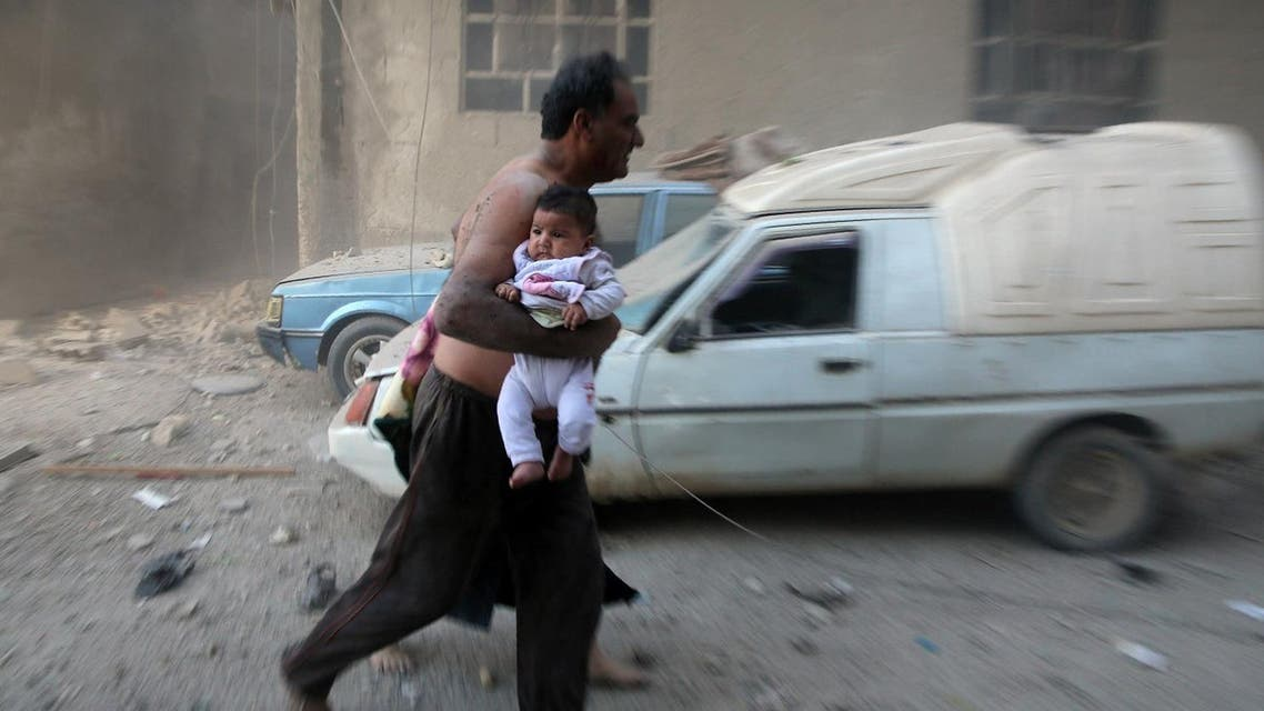 AFp A Syrian man carrying a child emerges from a dust cloud following a reported airstrike on Kafr Batna, in the rebel-held Eastern Ghouta area, on the outskirts of the capital Damascus, on September 30, 2016.