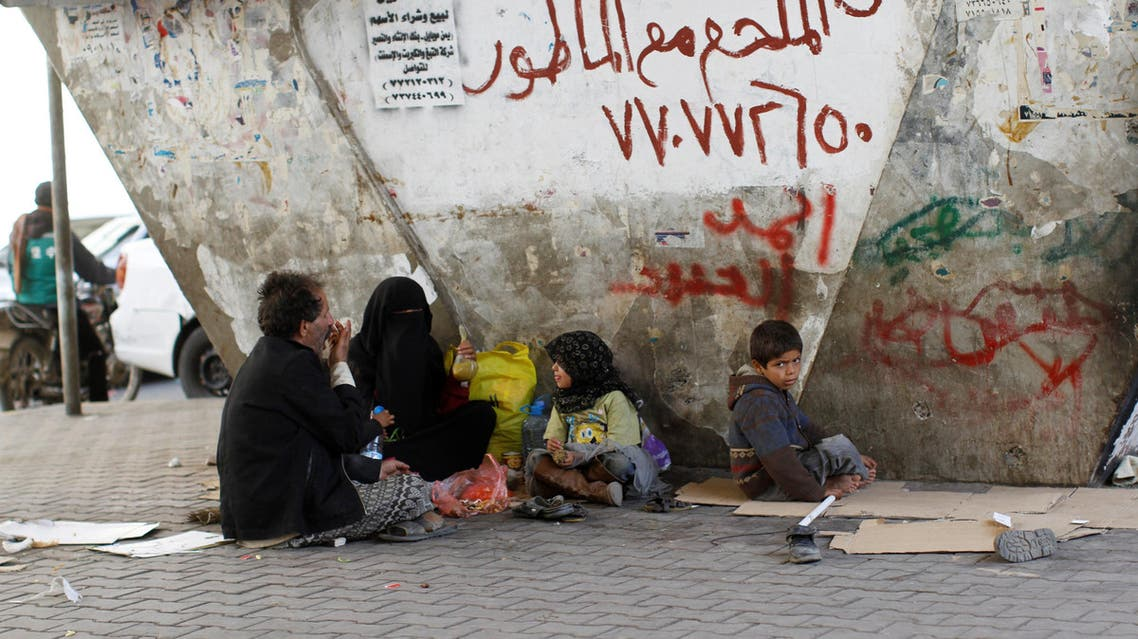 A homeless family sits on the street after having lunch, in Sanaa, Yemen, October 20, 2016. REUTERS