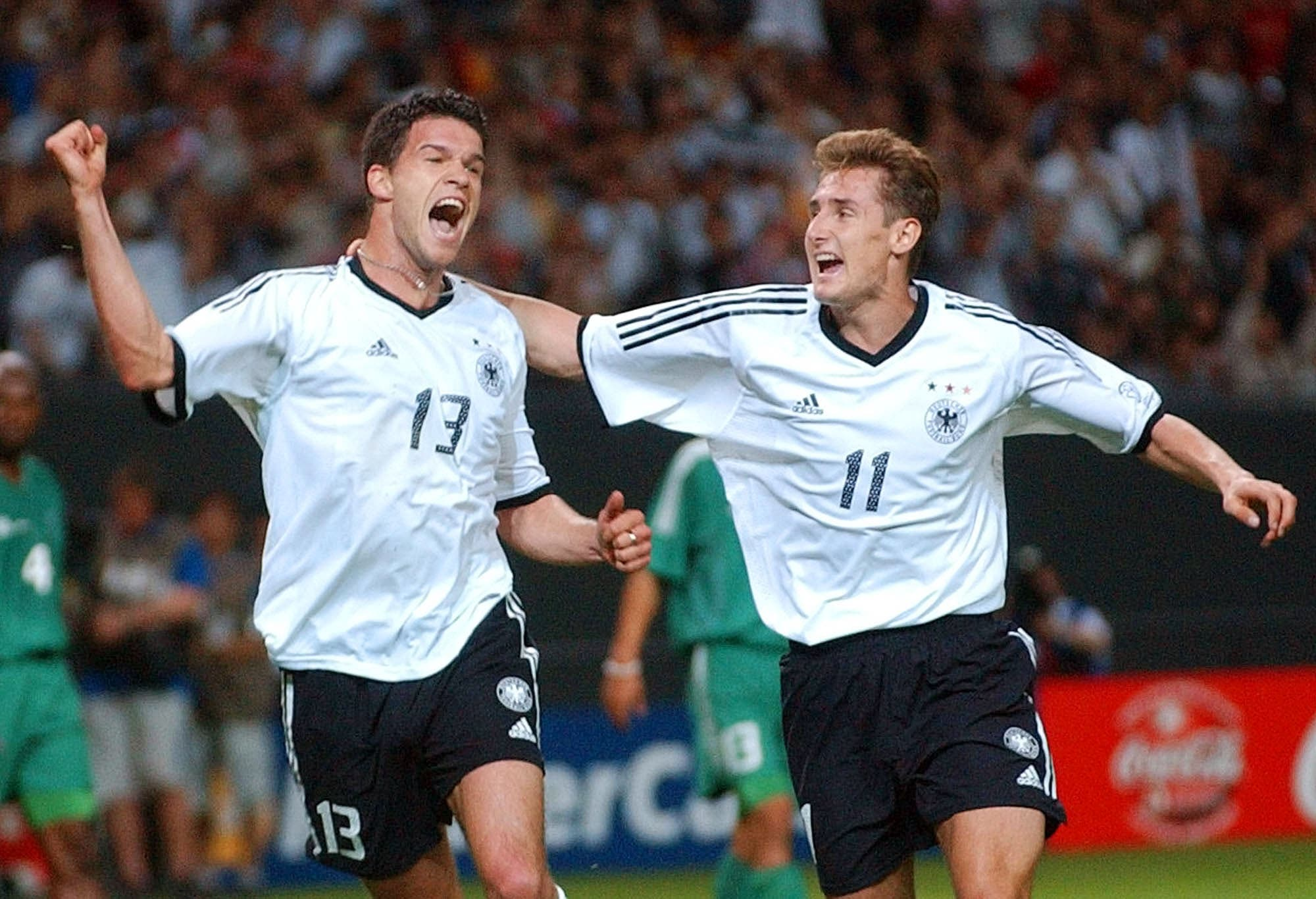 Germany's Michael Ballack, left, celebrates with teammate Miroslav Klose after scoring his sides third goal during the 2002 World Cup Group E soccer match between Germany and Saudi Arabia at the Sapporo Dome in Japan, Saturday June 1, 2002. The other teams in Group E are Ireland and Cameroon. (AP)