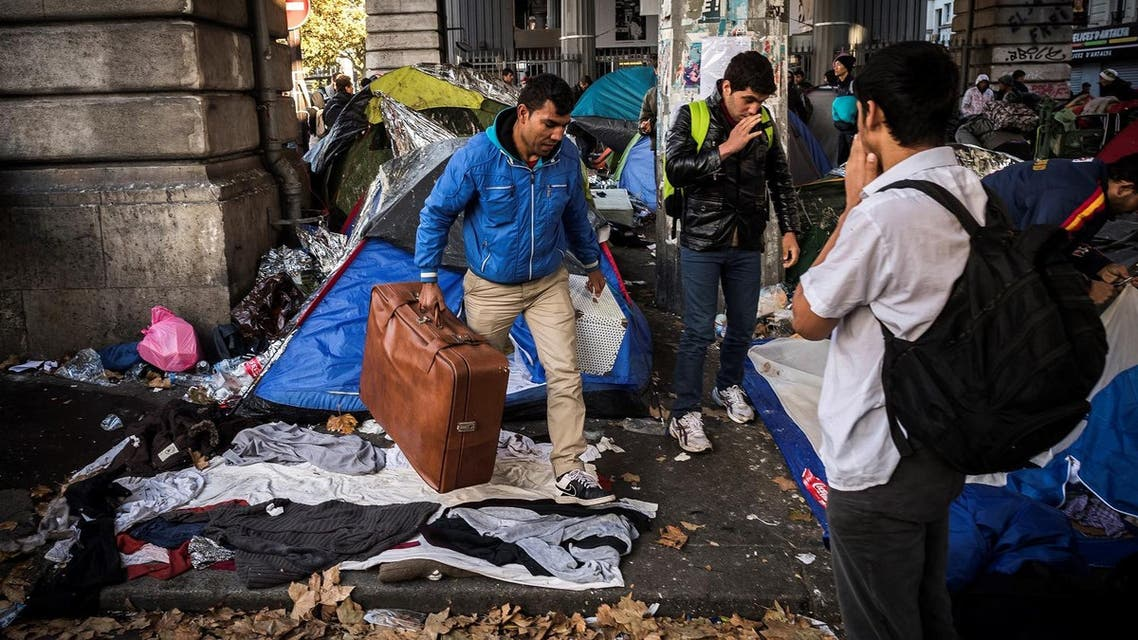Migrants carry their belongings at a makeshift camp at the Boulevard de la Villette, near the Jaures and Stalingrad metro stations, in northern Paris on October 31, 2016,
