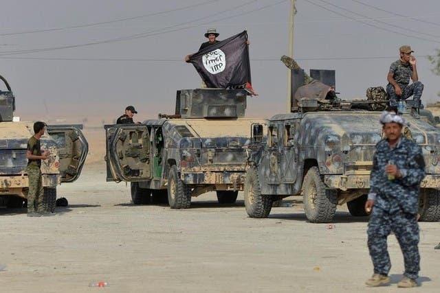 أحد أفراد الشرطة العراقية حاملا علم داعش بعد هجوم بجنوب الموصل