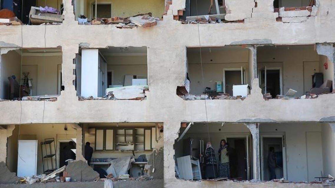 سكان يقفون داخل مبنى مدمر جراء تفجير سيارة ملغومة في مدينة ديار بكر بجنوب شرق تركيا