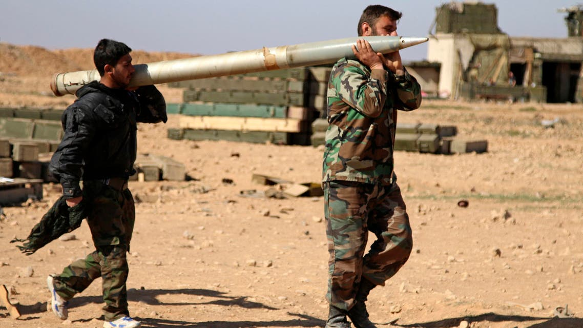 In this file photo taken on Wednesday, Feb. 17, 2016, soldiers from the Syrian army carry a rocket to fire at Islamic State group positions in the province of Raqqa, Syria. A two-pronged advance to capture key urban strongholds of the Islamic State, and the extremist group's self-styled capital of Raqqa has underlined a convergence of strategy between Washington and Moscow to defeat the extremist group, with Syria's Kurds emerging as the common denominator. (Alexander Kots/Komsomolskaya Pravda via AP, File)