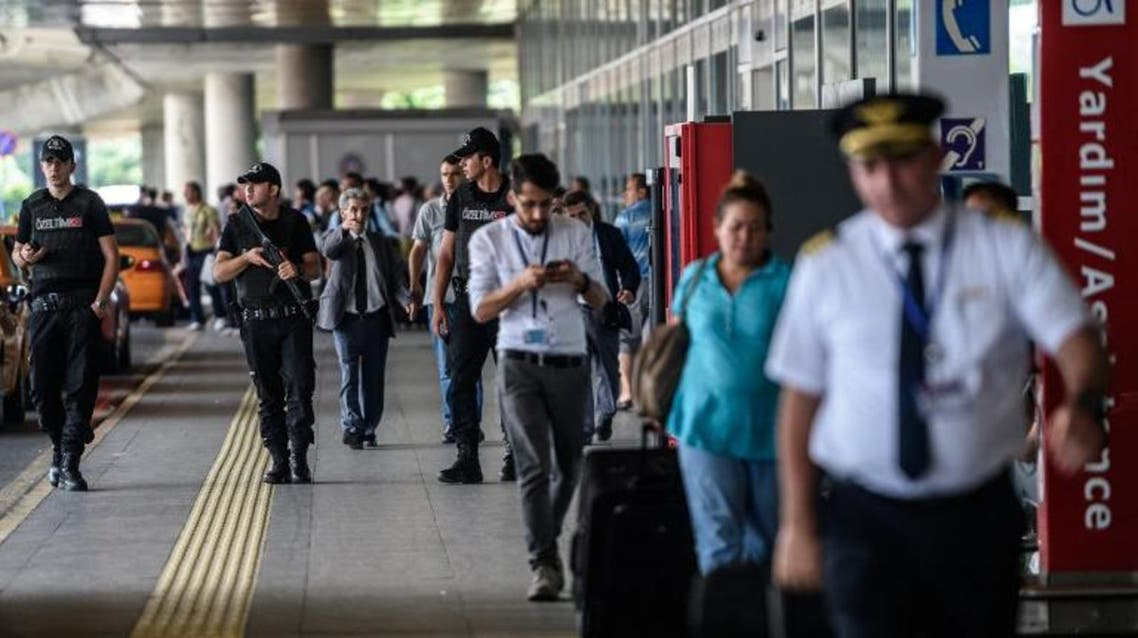 Turkish anti riot police officers stand guard as people walk nearby the explosion site at the Ataturk airport International terminal on July 1, 2016 AFP