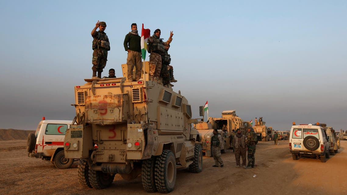 Peshmerga forces stand on a military vehicle in the town of Bashiqa, east of Mosul, during an operation to attack Islamic State militants in Mosul, Iraq, November 7, 2016