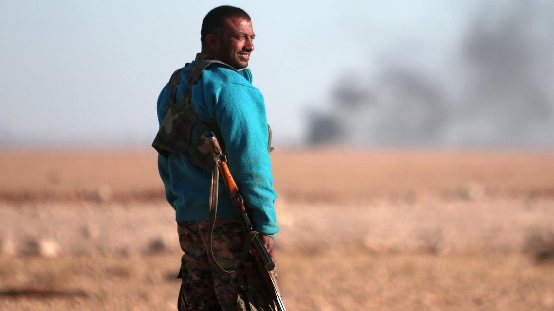 A Syrian Democratic Forces (SDF) fighter stands near rising smoke, north of Raqqa city. (Reuters)