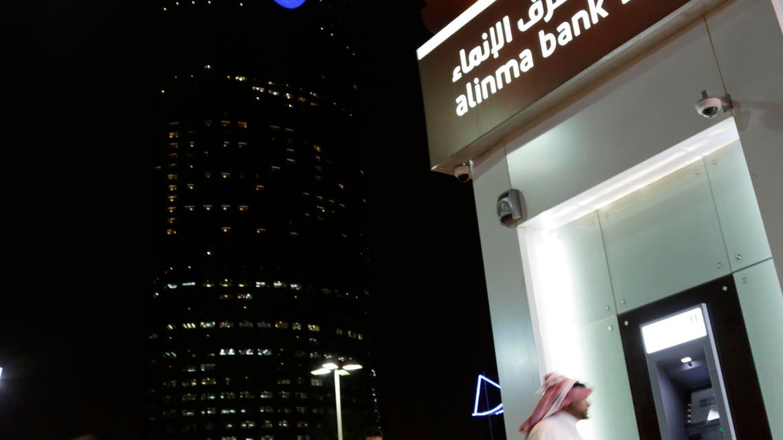 A Saudi man passes by a bank near the Kingdom Tower  in Riyadh, Saudi Arabia. (AP)
