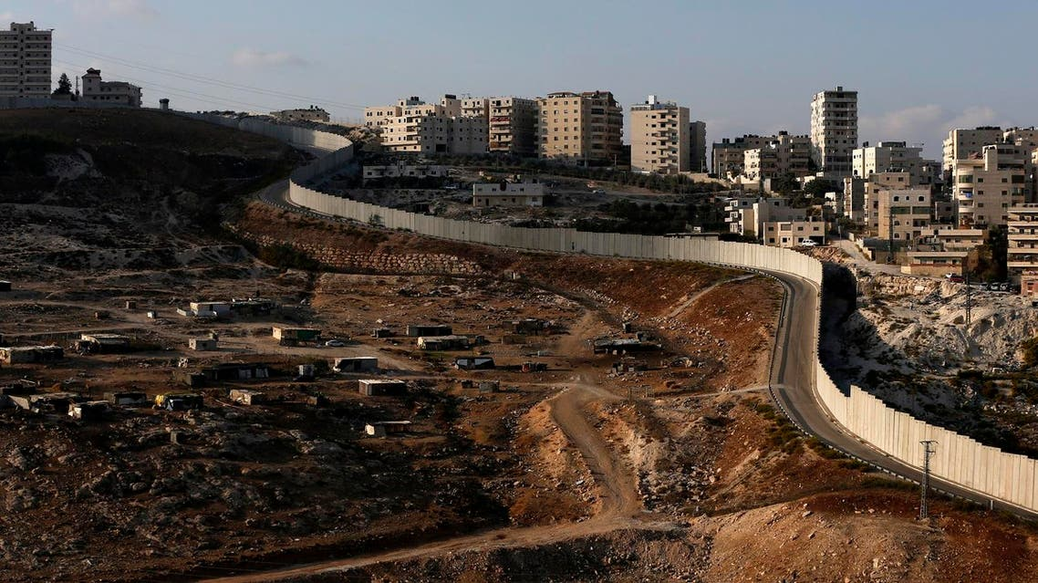 A picture taken on October 18, 2016 from the east Jerusalem Arab neighbourhood of Issawiya shows a view of the Palestinian Shuafat refugee camp (R) behind the controversial Israeli separation wall.  AHMAD GHARABLI / AFP