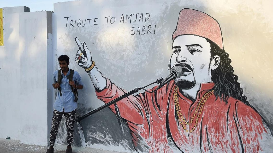 """A Pakistani student takes a photograph of his friend next to a wall image of late Sufi musician Amjad Sabri in Karachi on June 27, 2016. One of Pakistan's best known Sufi musicians Amjad Sabri was shot dead by unknown assailants riding a motorcycle in Karachi on June 22, triggering an outpouring of grief over what police described as an """"act of terror"""". ASIF HASSAN / AFP"""