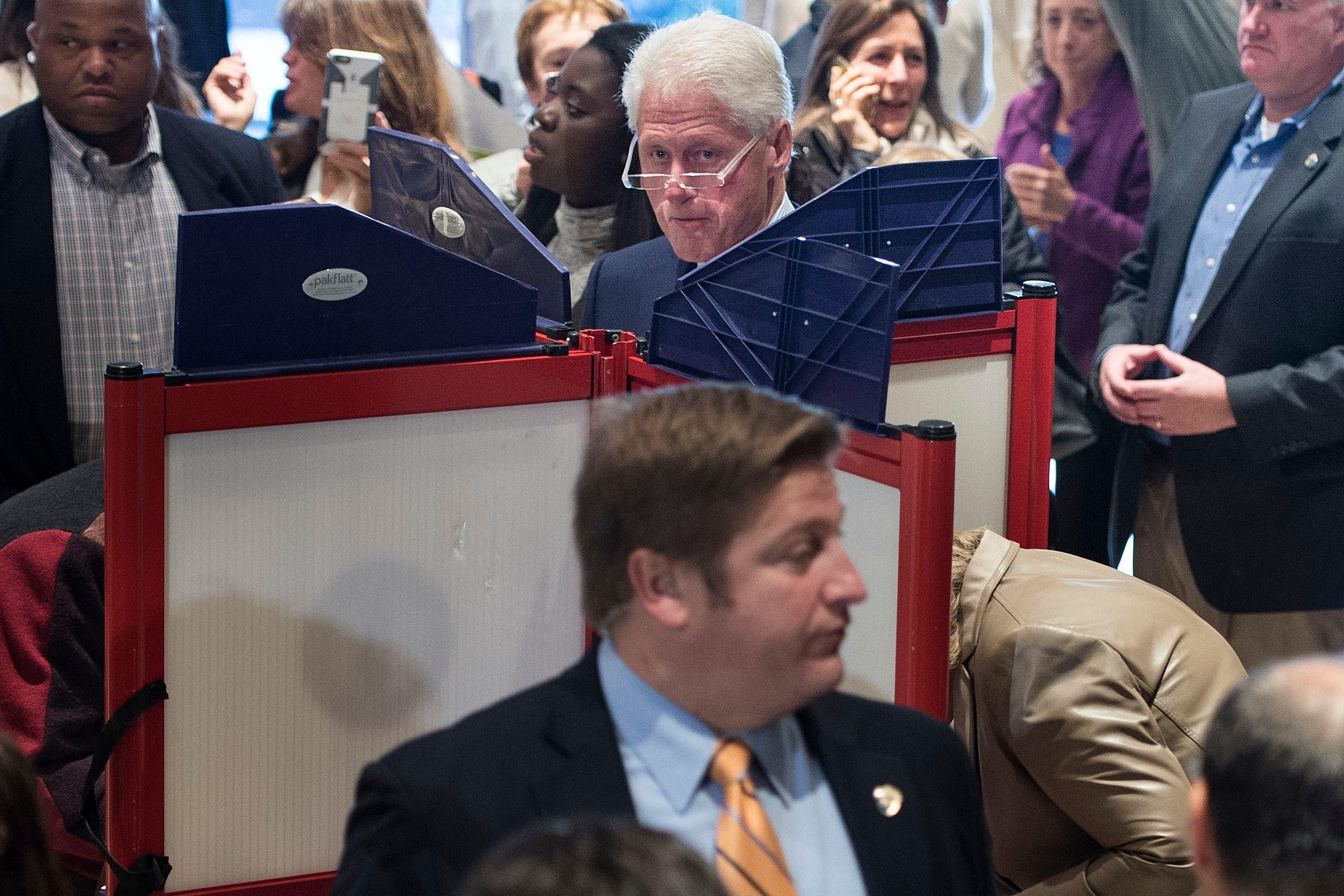 هیلاری کلینتون در حال پر کردن برگ رای و بیل کلینتون در تصویر