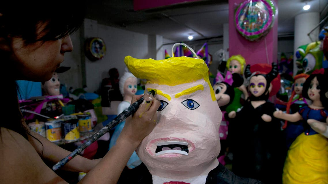 """In this Friday, July 10, 2015 file photo, Alicia Lopez Fernandez paints a pinata depicting Donald Trump at her family's store """"Pinatas Mena Banbolinos"""" in Mexico City. (AP)"""