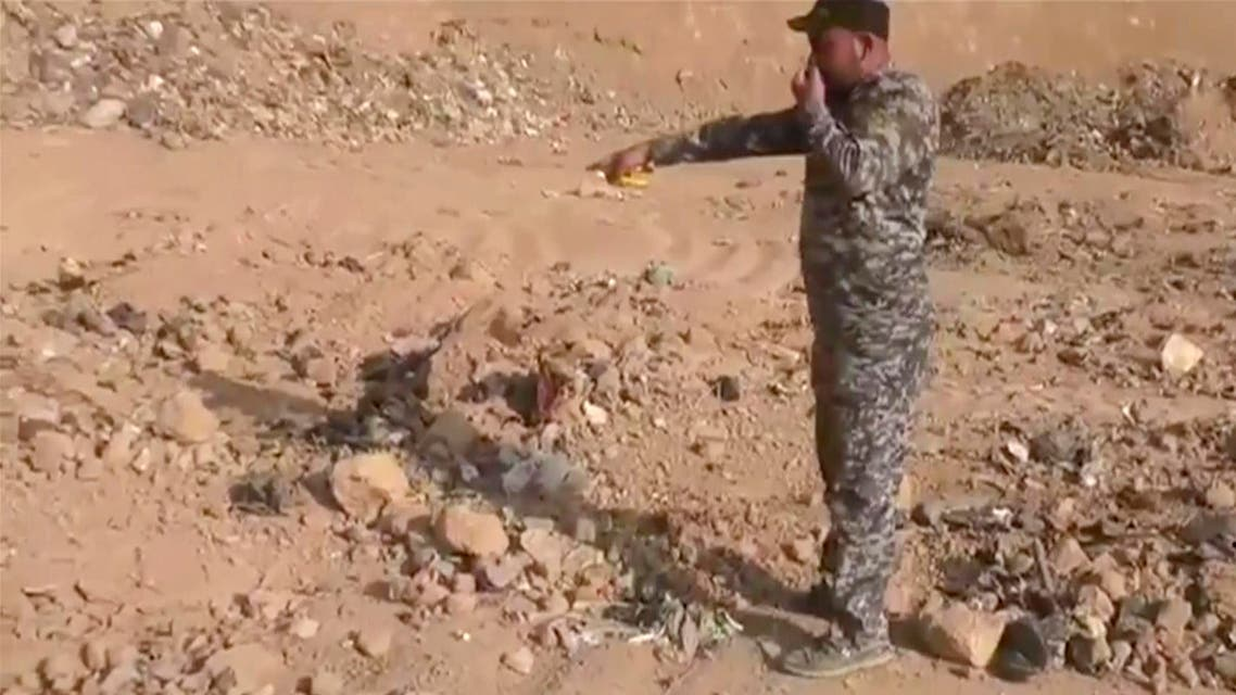 In this Monday, Nov. 7, 2016 frame grab from video, an Iraqi federal police officer holds his nose as he points towards a mass grave in Hamam al-Alil, Iraq. (AP)
