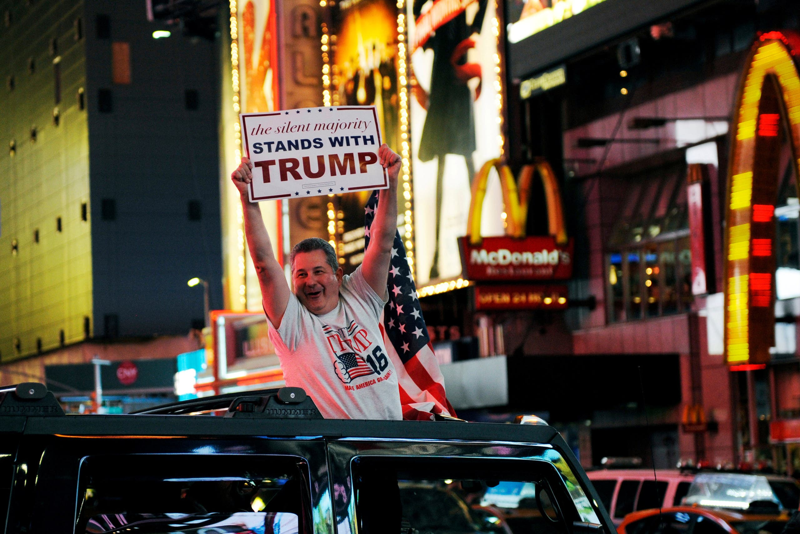 A man leans out of a Hummer shouting words in support of U.S. Republican presidential nominee Donald Trump while driving through Times Square in New York, U.S., November 9, 2016. (Reuters)