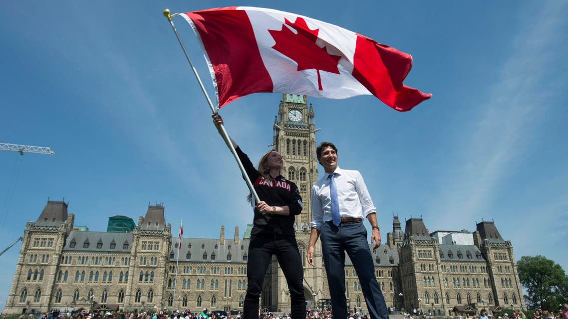 Canadian Prime Minister Justin Trudeau looks on as athlete Rosie MacLennan waves the Maple Leaf after being named as the flag bearer for the upcoming Summer Olympics Thursday July 21, 2016 in Ottawa.  AP