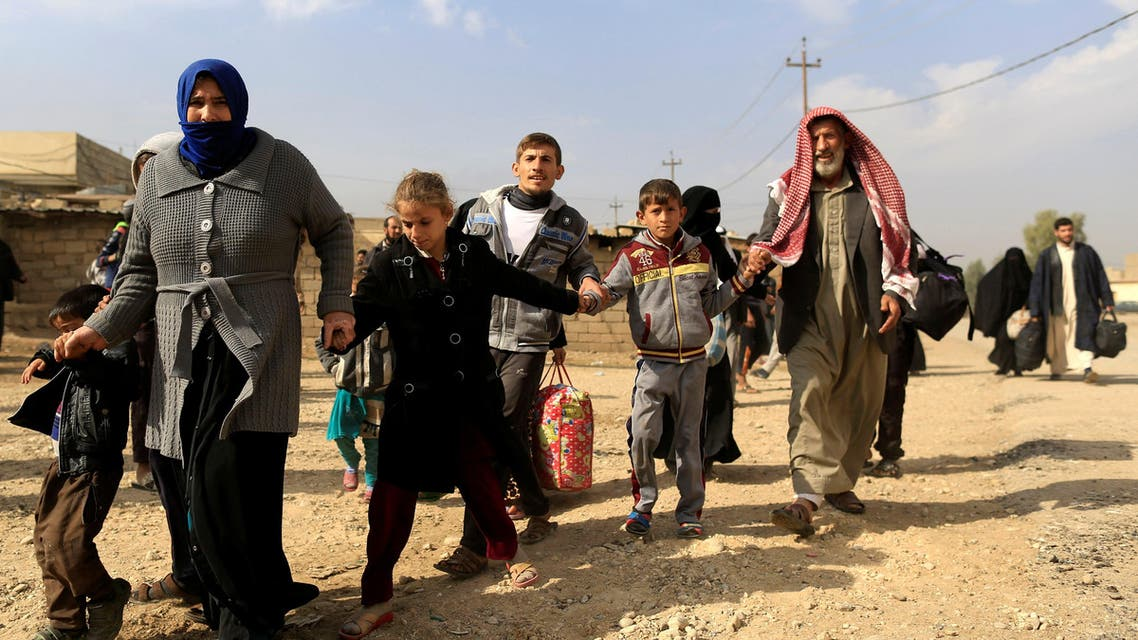 A family fleeing fighting between the Islamic State and Iraqi army in Intisar district of eastern Mosul, make their way to safer territory, Iraq November 8, 2016. (Reuters)