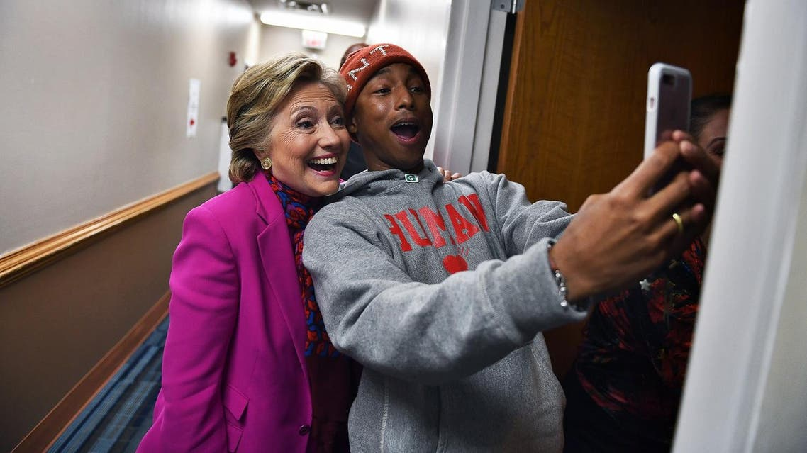 US Democratic presidential nominee Hillary Clinton poses with singer Pharrell Williams for a selfie backstage before a campaign rally in Raleigh, North Carolina, on November 3, 2016. (AFP)