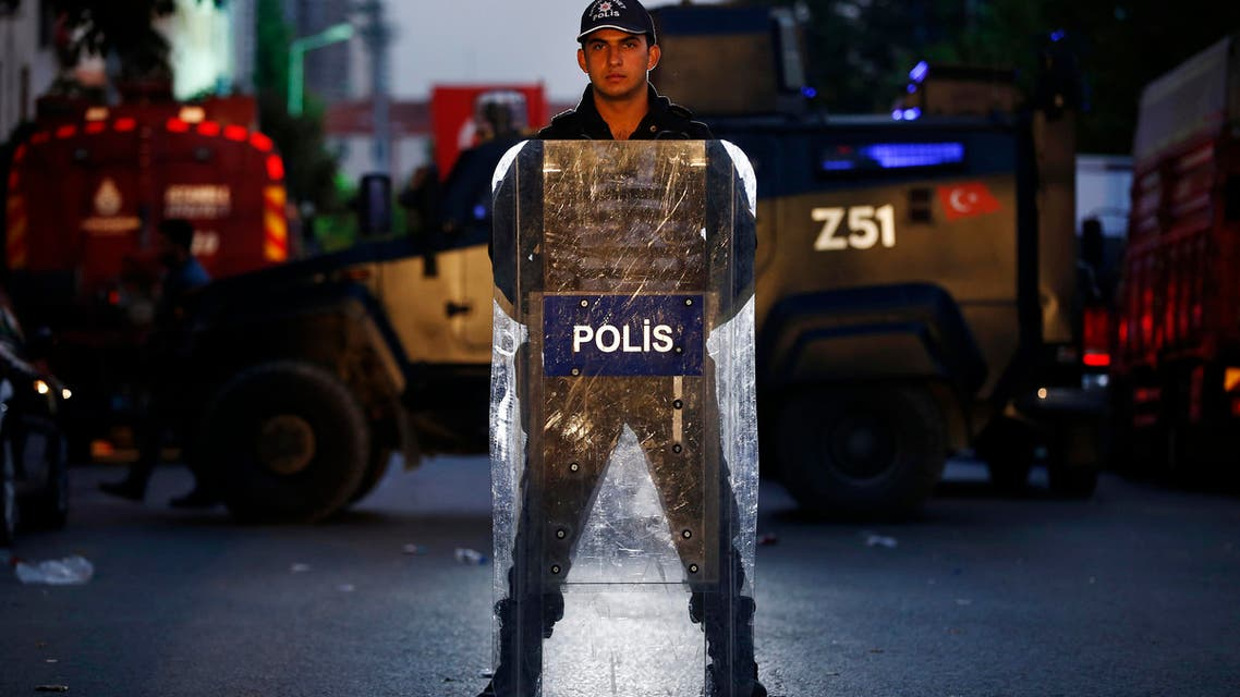 A Turkish police officer stands behind his shield as he secures the scene of a blast in Istanbul, Thursday, Oct. 6, 2016. AP
