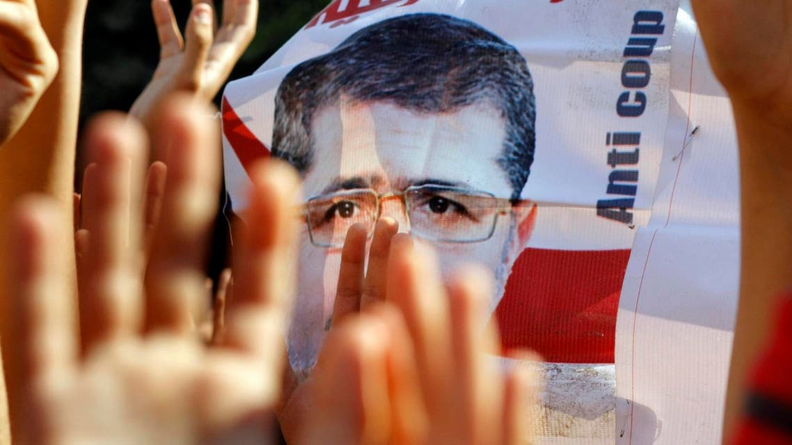 Supporters of Egypt's ousted President Mohammed Morsi raise his poster and their hands with four raised fingers, which has become a symbol of the Rabaah al-Adawiya mosque (File Photo: AP/Amr Nabil)