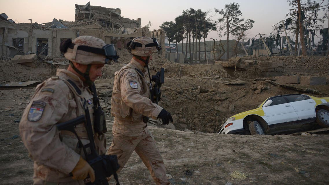 Croatian soldiers from the NATO coalition are walking past a crater from a bomb blast as they inspect the site of an attack targeting the German consulate in Mazar-i-Sharif on November 11, 2016. afp