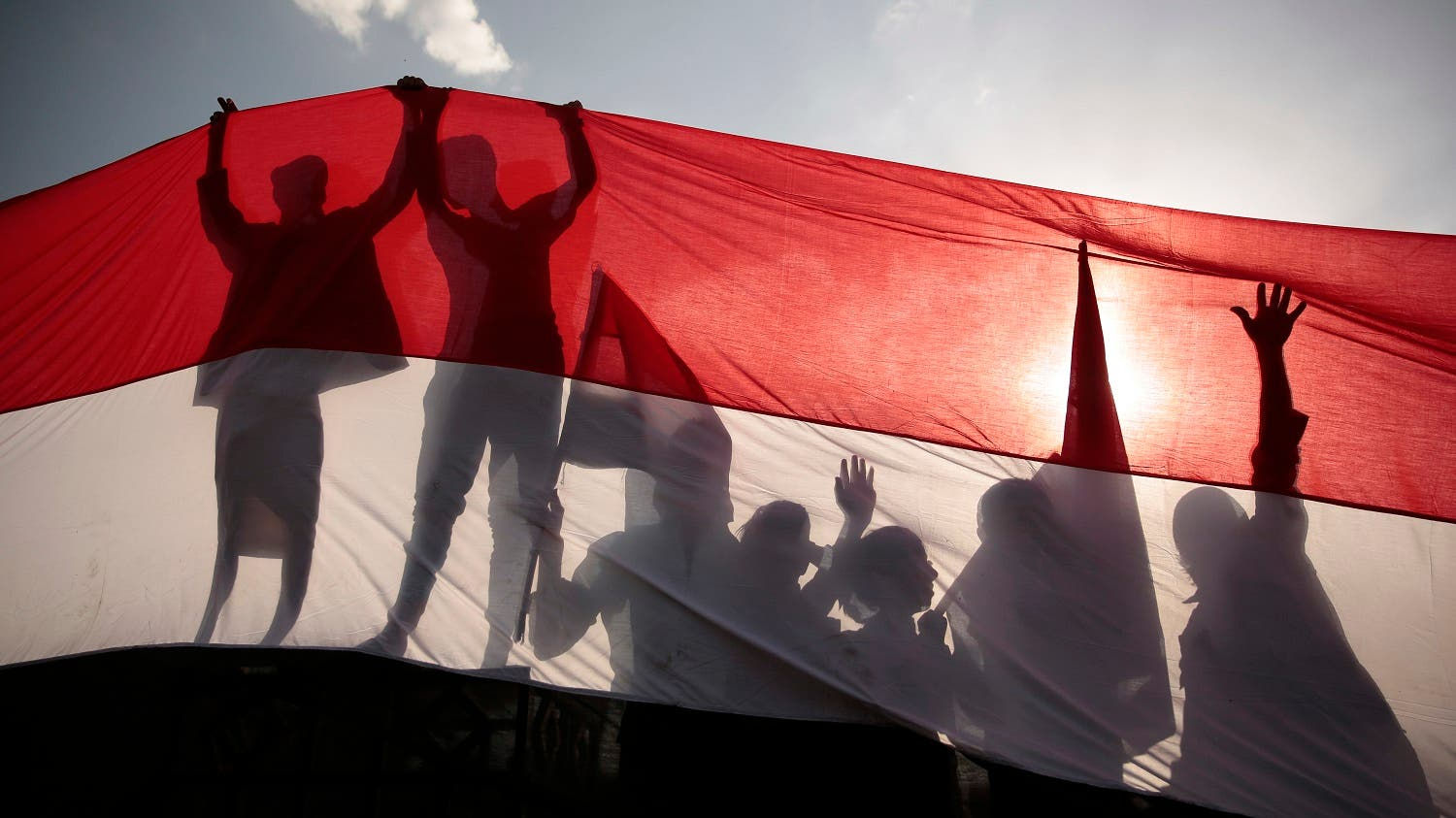 Men are silhouetted against a large representation of the Yemeni flag as they attend a ceremony to mark the anniversary of North Yemen's Sept. 26, 1962 revolution. (AP_