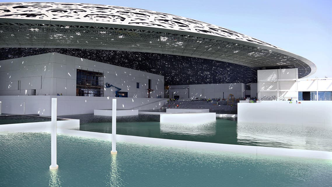 """A handout picture taken on May 24, 2016, and made available on June 15, 2016, by Abu Dhabi's Tourism Development and Investment Company (TDIC) shows Abu Dhabi's Louvre museum, designed by French architect Jean Nouvel, surrounded by sea water. The museum has been surrounded by sea water in a major step towards completion of the ambitious project, TDIC said on June 15, 2016. The contractor has begun removing temporary sea protection walls used during the main construction phase, allowing the """"integration of the sea"""" with the museum, the developer said. HO / TDIC / AFP"""
