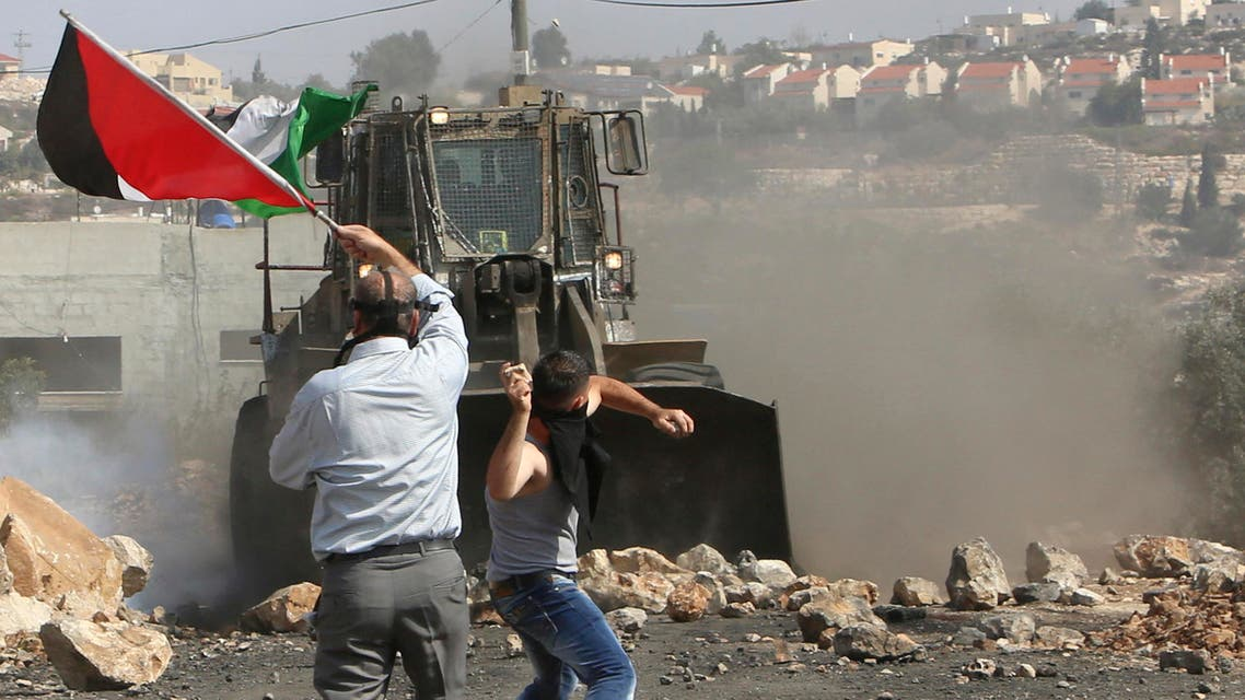 A Palestinian boy throws stones at an armored wheel loader of the Israeli Defense Forces (IDF) during clashes following a protest against the near-by Jewish settlement of Qadomem, in the West Bank village of Kofr Qadom near Nablus October 17, 2014. reuters