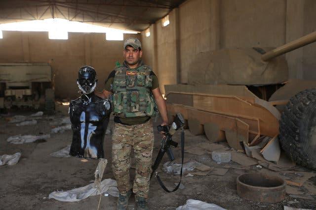 أحد عناصر القوات العراقية يحمل تمثالاً استعمله دعش للتمويه