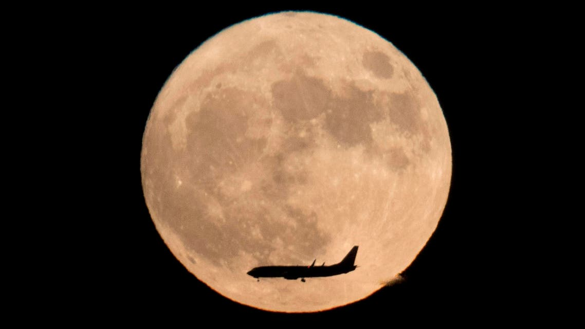 A jet plane flies across the moon seen from Beijing, China, Monday, Nov. 14, 2016. The brightest moon in almost 69 years lights up the sky on Monday in a treat for star watchers around the globe. The phenomenon is known as the supermoon. (AP)