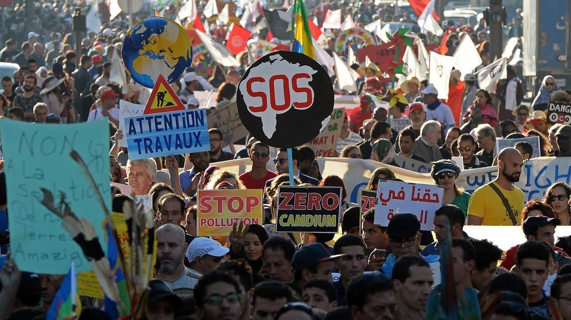 Moroccan and international demonstrator shout slogans and hold placards during a demonstration against climate change and calling for environmental action to protect the planet during a protest in Marrakesh on the sidelines of the COP22 climate conference on November 13, 2016. FADEL SENNA / AFP
