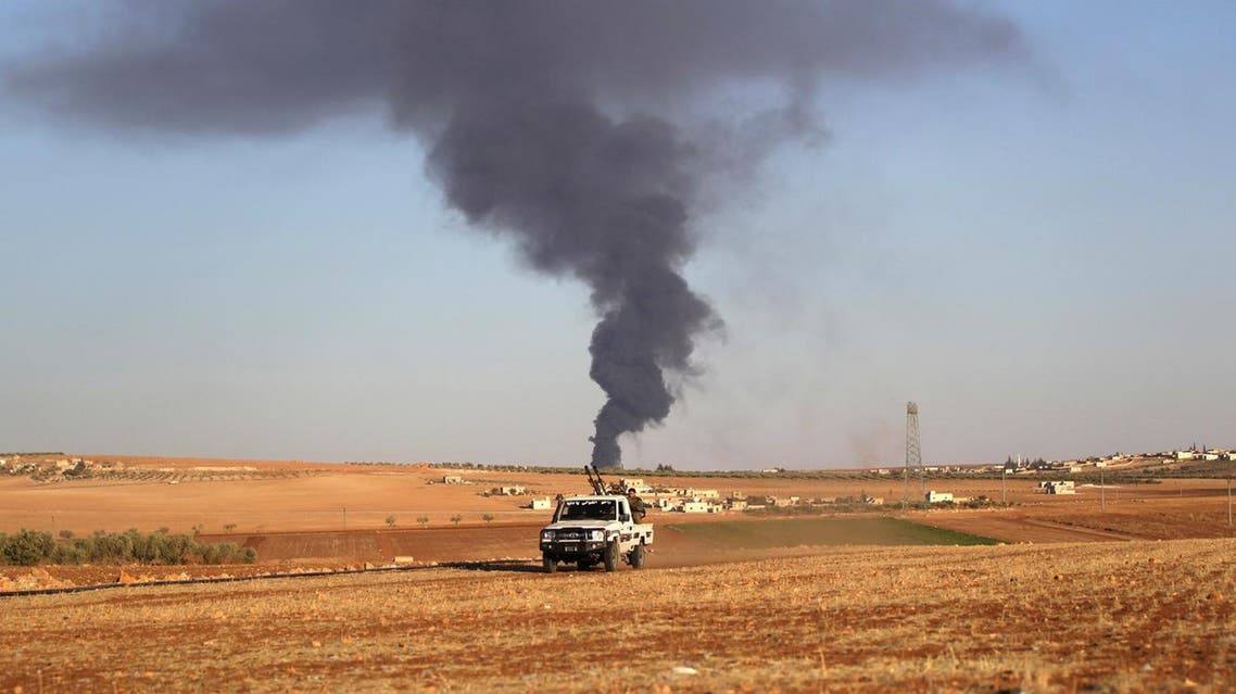 Rebel fighters ride a military vehicle near rising smoke from al-Bab city, northern Aleppo province. (Reuters)