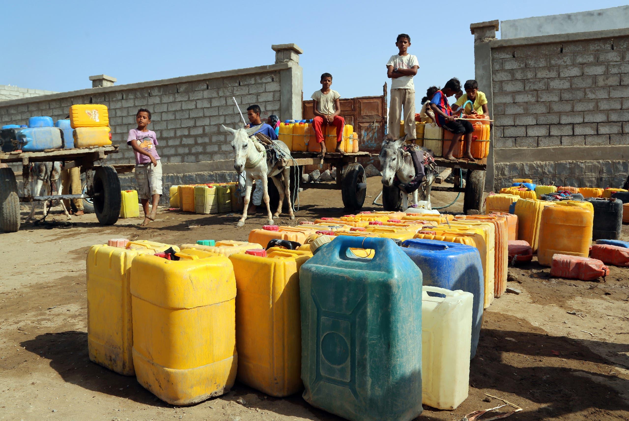 أطفال يمنيون يعبئون المياه في الحديدة
