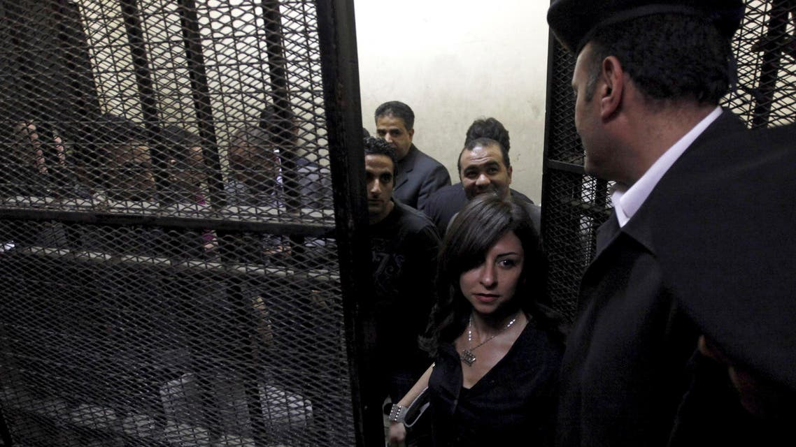 Activists, accused of working for unlicensed non-governmental organizations (NGOs) and receiving illegal foreign funds, stand in a cage during the opening of their trial in Cairo March 8, 2012. REU