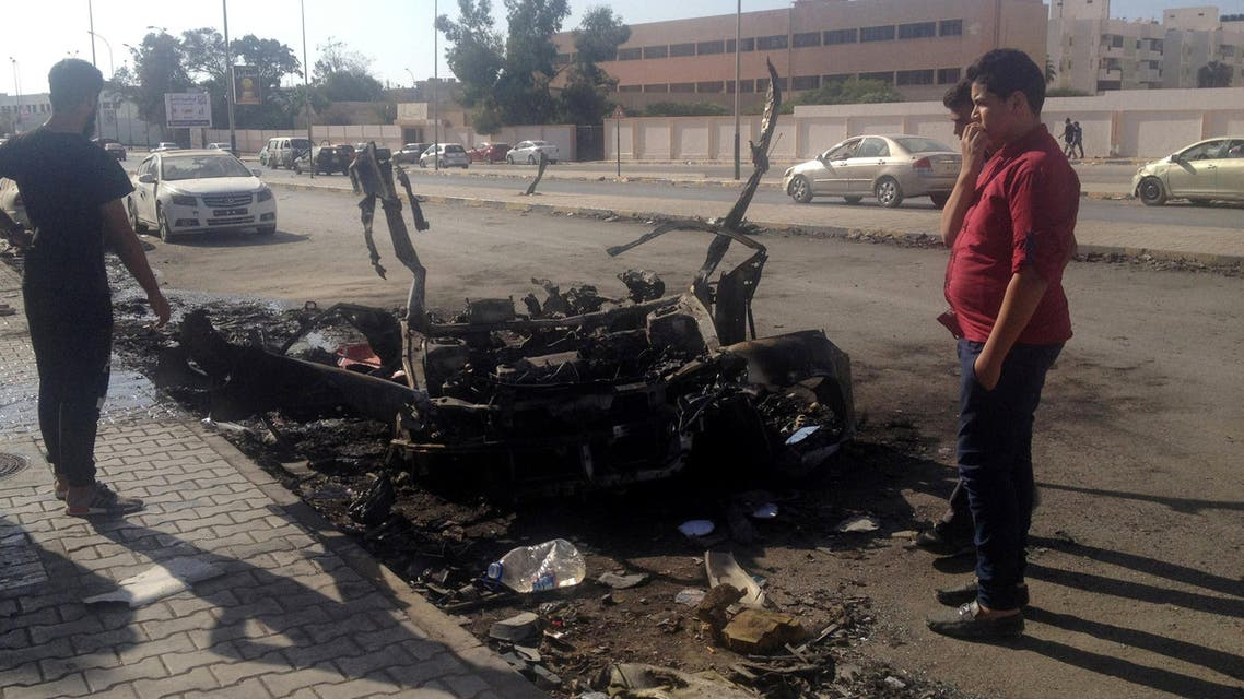 People stand around the wreckage of a car that exploded late on Saturday in Libya's eastern city of Benghazi October 30, 2016 بنغازي ليبيا