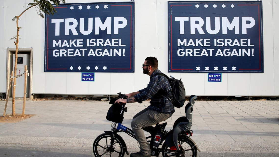 A man cycles past signs bearing the name of U.S. President-elect Republican Donald Trump in Tel Aviv, Israel November 14, 2016. REUTERS